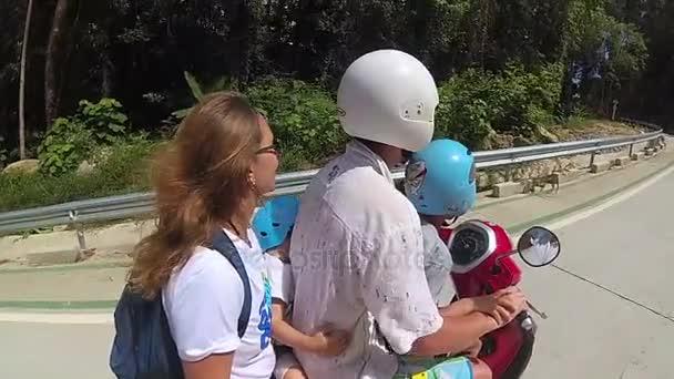 šťastná rodina jezdí na motorce v tropech