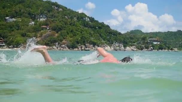 Mann schwimmt bei sonnigem Wetter im offenen Meer