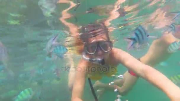 Bambina e fare il bagno nel mare con i pesci. Immersioni subacquee in maschere