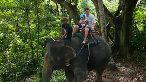 Phangan, Thajsko - Březen 30,2017: Rodina, jízda na slonech v tropickém pralese