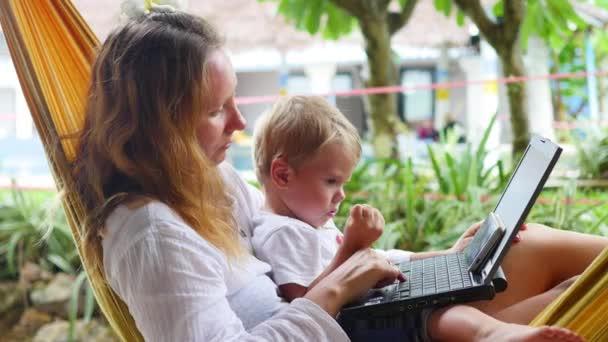 dívku a dítě pracuje na notebook a smartphone leží v houpací síti