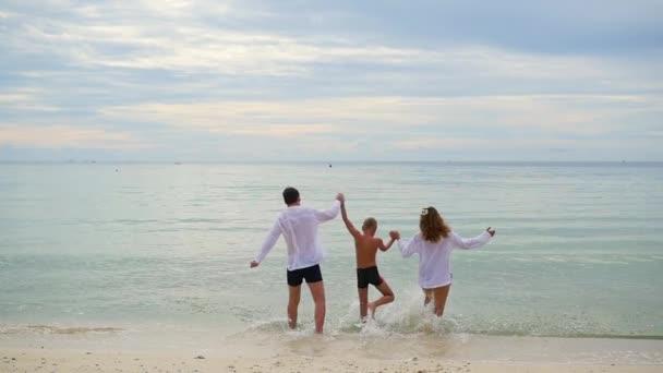 glückliche Familie Händchen haltend am Ufer entlang laufend. um im Wasser zu laufen und Spritzer zu erzeugen