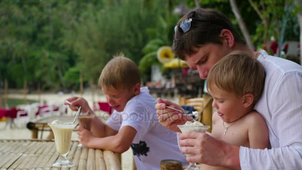 The family eats ice cream in a cafe on the beach