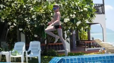 Kid playing ball in the pool. sports outdoors. Jump into the pool with splashes