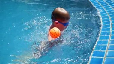 Child is playing ball in the pool. Sports in the open air.
