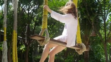 A girl swinging on a rope swing on the beach