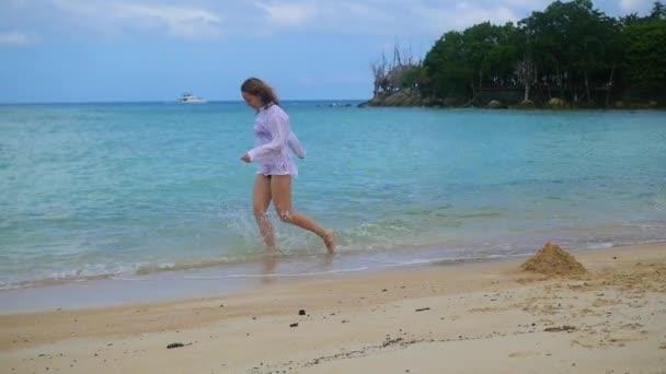 Mladá dívka se táhne podél pláže pobřeží, vytváří proud vody