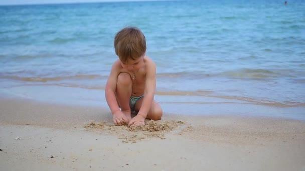 Kind spielt an einem sonnigen heißen Tag mit Sand am Strand
