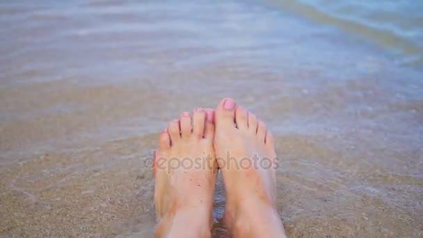 Dámské nohy šplouchání v mořské vodě na pláži. Closeup