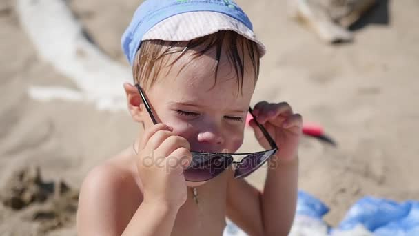 The child tries to wear sunglasses. The beach, a Sunny hot day