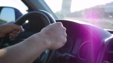 the guy drives a car on a Sunny day. The time of sunset. Hands and steering wheel closeup