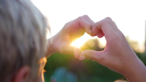 člověk, aby srdce s rukama na slunci. Silueta ruku ve tvaru srdce s uvnitř západ slunce.