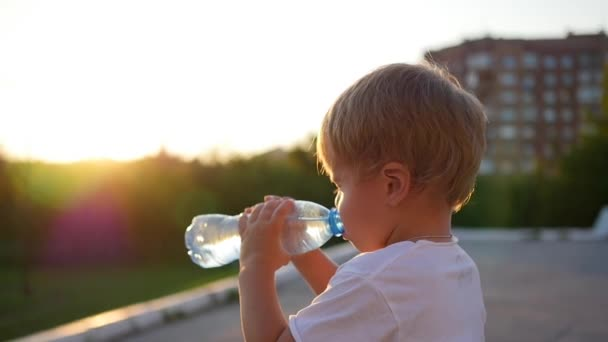 baby drinks water from bottle outdoors. Sunset time