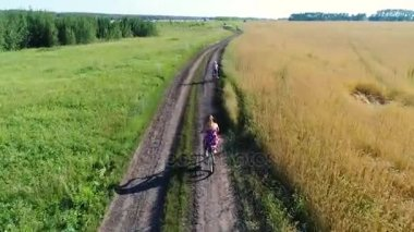 Girl in a dress with a child riding a Bicycle along fields of wheat. Shooting with the drone. Beautiful landscape from a height