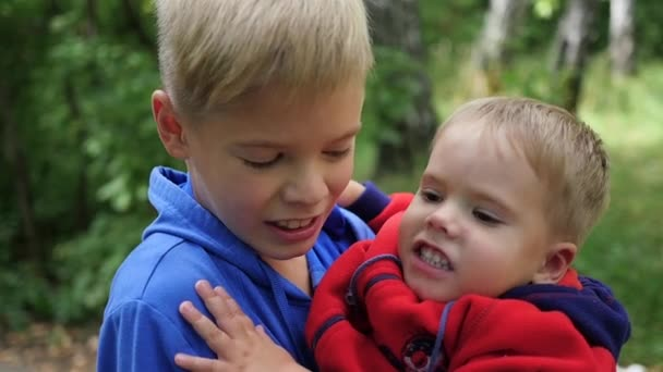 The boy hugs his younger brother and holds him on his arms