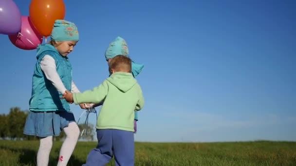 Šťastné děti krouží držel ruku v parku s balónky
