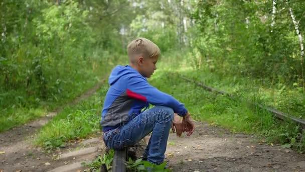 A lonely teenage Boy sitting on railroad tracks
