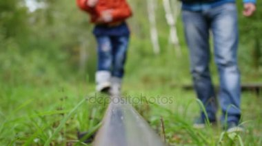 Closeup. The legs are on train tracks. Guy holds a child walking down the railroad