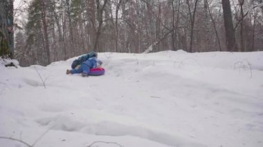 Two children ride on a snowy hill on a sled. Children fall with a sled. Sports and outdoor activities