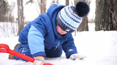 A little child playing with snow in winter Park. Sunny winters day. Fun and games in the fresh air.