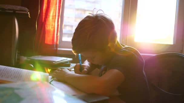 Chlapce, který seděl na školní stůl a dělá svou práci. Školní vzdělání. Paprsky slunce přes sklo.