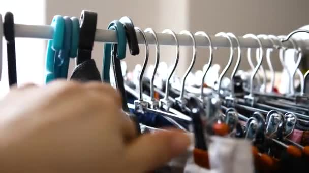 Zblízka. Dívka si vybírá oblečení na ramínko v úložišti. Značkové oblečení, módní oblečení