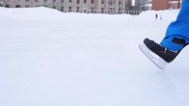 Čepel bruslí prořezává led. Hokejista dělá brzdy na ledě. Detailní záběr na hokejové brusle.
