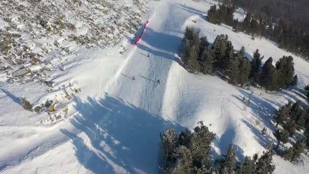 Lyžařský svah. Lyžaři a snowboardisté se valí po trati. Letecká fotografie lyžaře sjíždějícího po široké sjezdovce