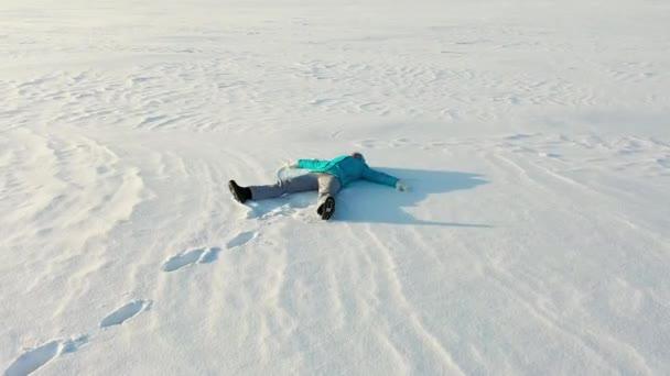 Děvče udělá postavu sněžného anděla na mýtině v lese. Letecká fotografie dívky ležící ve sněhu.