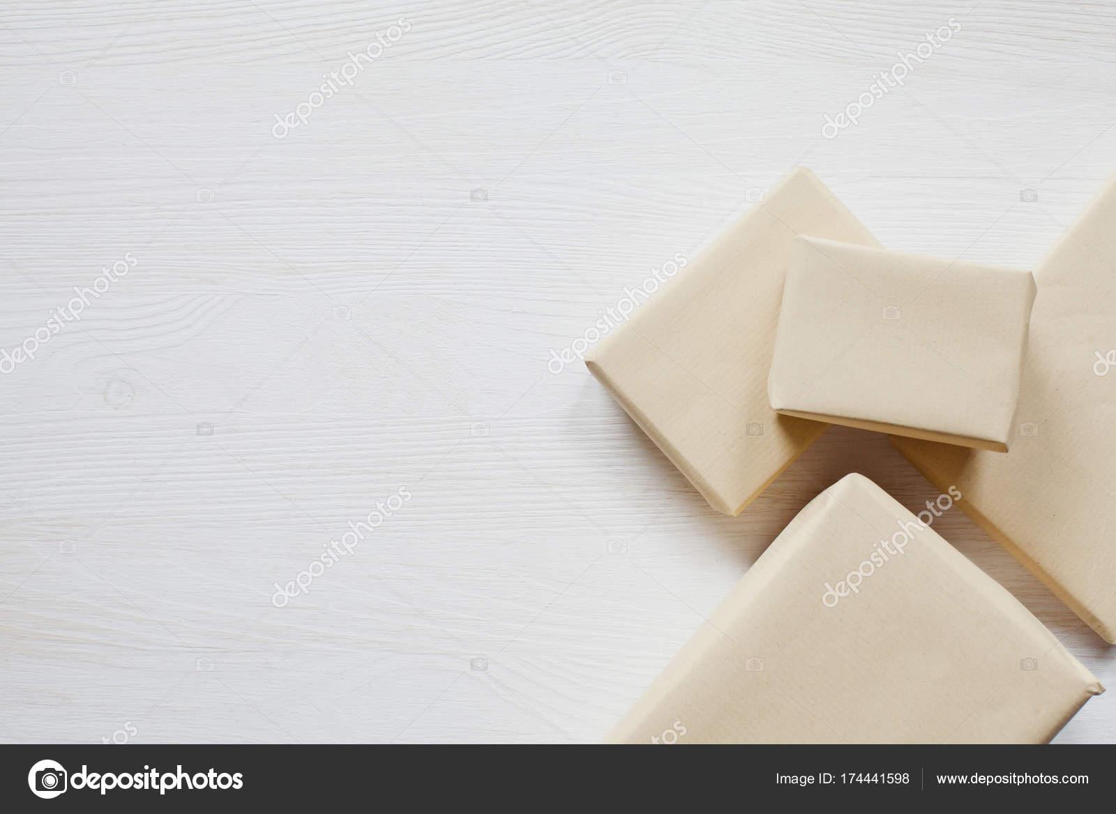 Boîtes enveloppés rustiques sur bureau blanc en bois