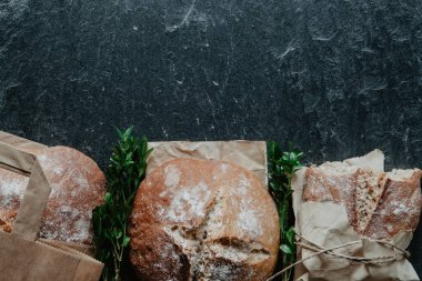 Healthy bread freshly from oven with packing paper and boxwood o
