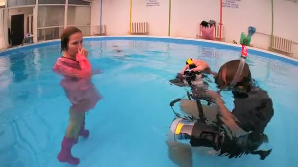 A woman in a pink raincoat and rubber boots posing for underwater photographers in the pool