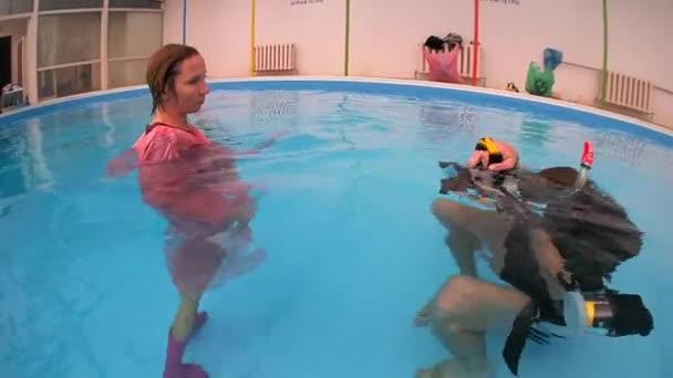 Egy nő, egy rózsaszín esőkabátot és gumi csizma, pózol a medence víz alatti fotósok