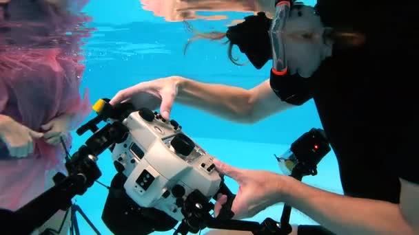 Chlapec v brýle, plavání pod vodou a pózuje pro fotografování pod vodou v bazénu