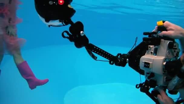 Žena v růžové plášť do deště a gumové boty představují pro podvodní fotografy v bazénu