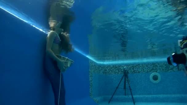 Flicka i sjöjungfru dräkt bär poser under vattnet i poolen– stockfilm eebf27136ef30