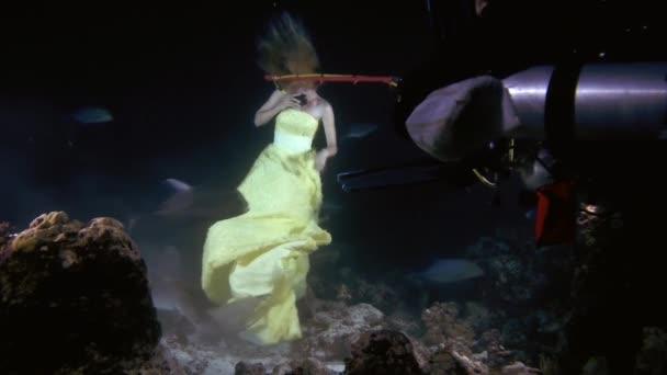 Taucher verschafft einer jungen schönen Frau in einem gelben Kleid Luft, die unter Wasser mit einem braunen Ammenhaie (nebrius ferrugineus) posiert)