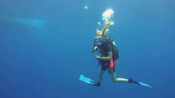 Indischer Ozean, Malediven - März 2017: junge Sporttaucherin schwimmt im blauen Wasser
