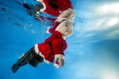A little boy in Santa's cost swims underwater in the pool