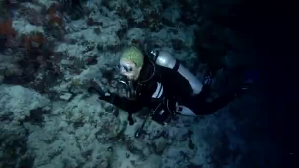 Indischer Ozean, Malediven, Asien - März 2018: Die junge schöne Sporttaucherin schwimmt in der Nähe von Korallenriffen und blickt auf den Computer. Nachttauchen, Indischer Ozean, Malediven