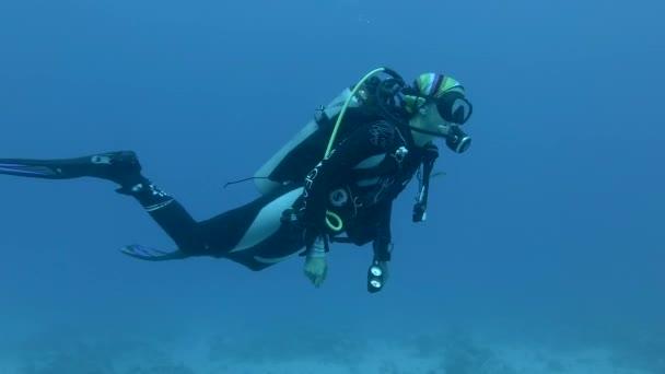 Nahaufnahme einer Taucherin, die im blauen Wasser schwimmt. Unterwasseraufnahmen, rotes Meer, Ägypten