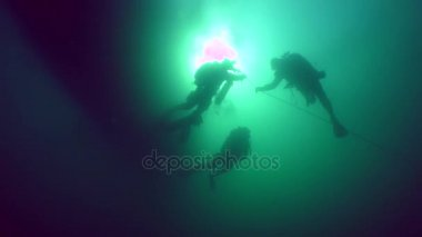 Divers on the background of a water surface and a solar disk.