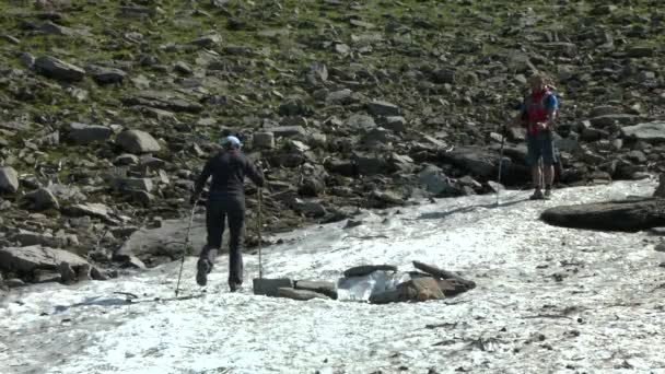 Tourists go up the dirty snow that has remained since last winter.