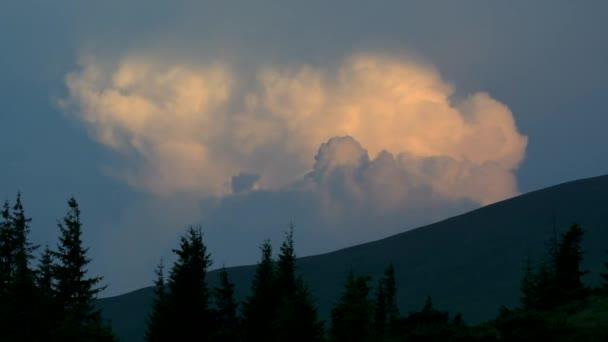 Mraky osvětluje zapadající slunce nad vrcholky hor.