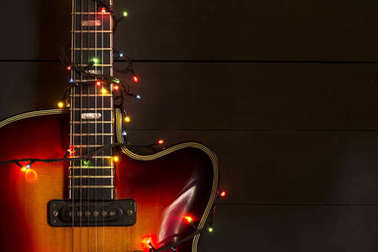 Old electric guitar with a lighted garland on a dark background. Greeting, Christmas, New Year greeting card. Copy space.