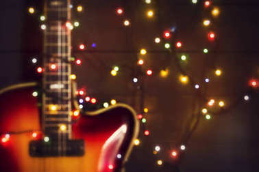 Old electric guitar with a lighted garland on a dark background. Out of focus background. Greeting, Christmas, New Year greeting card. Copy space.
