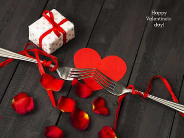 Red paper hearts, rose petals and fork with ribbon. Dark wooden background. Copy space. Valentine's Day.