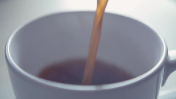 Close up of pouring coffee into white cup
