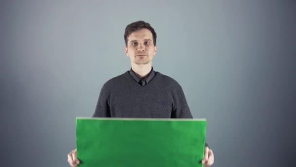 Fiatal ember, aki egy üres poszter szürke háttér