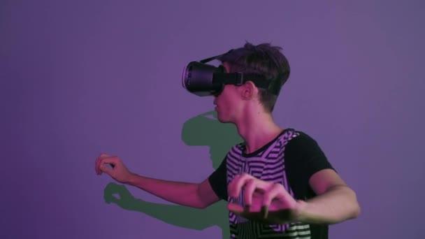 Mladý muž s fialovou ofinou pomocí vr brýle dělají gesta rozhlížel fialové pozadí